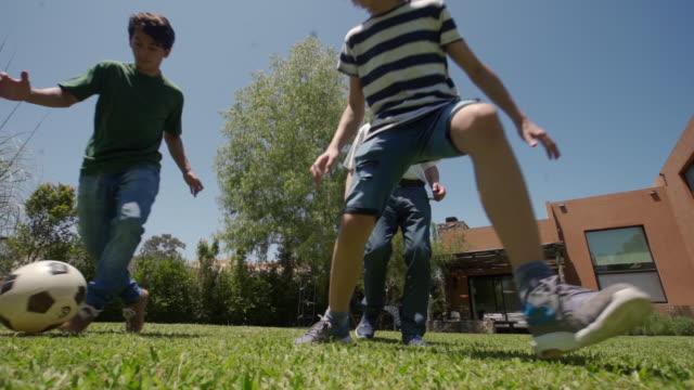 stockvideo's en b-roll-footage met opa en kleinzoon spelen voetbal buiten - latijns amerikaanse en hispanic etniciteiten