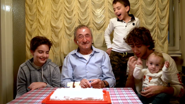 Grandpa blowing out the candles on his birthday cake