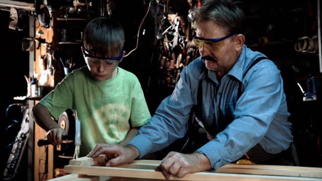 Grandpa carpenter makes a window with his grandson video