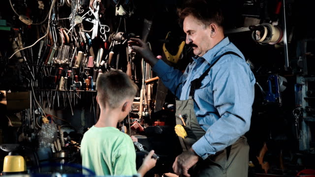 Grandpa carpenter with his grandson in the workshop video