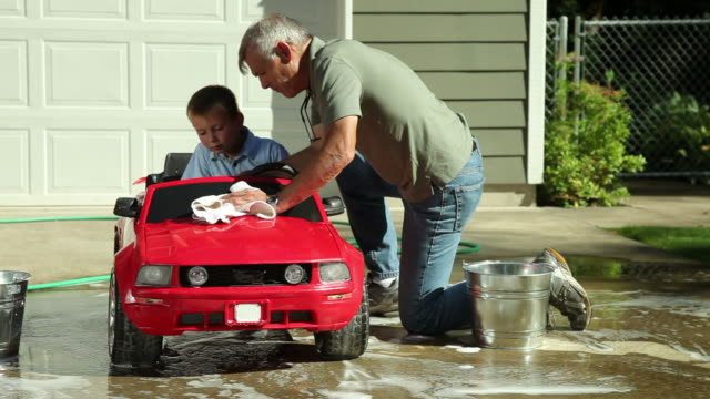 grandpa helps wash grandson's car - baby boomer stock videos and b-roll footage