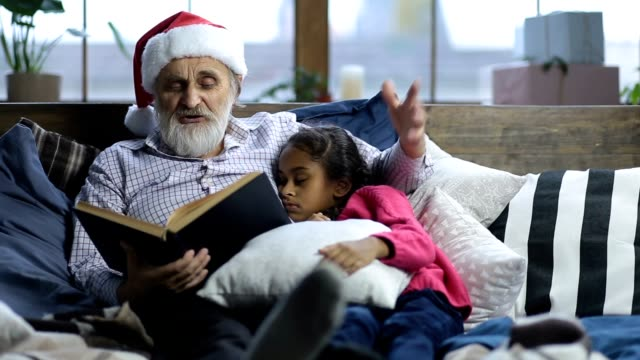 Grandpa reading bedtime story to sleepy child Caring grandfather with grey beard and in santa hat reading a book to his sleepy cute mixed race granddaugther as they lie in bed on christmas eve. Affectionate grandpa cuddling his adorable girl while reading bedtime story at home on Xmas. granddaughter stock videos & royalty-free footage