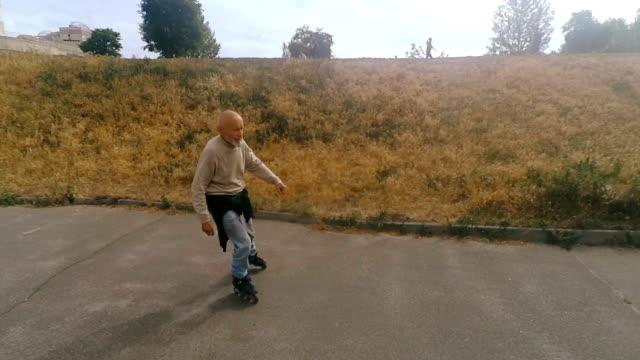 grandpa rolls on roller with a dog of the griffon breed - wytworzony przedmiot filmów i materiałów b-roll