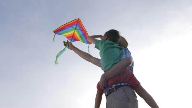 Grandpa teaching grandsonto fly kite