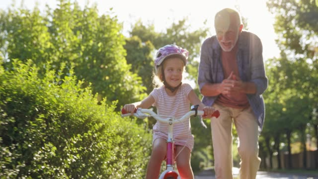 SLO MO DS Grandpa teaching young granddaughter how to ride a bike and clapping his hands with joy Wide slow motion low angle front dolly shot of a little girl riding her bike for the first time and her grandfather is running next to her and clapping his hands with joy and encouragement. Shot in Slovenia. granddaughter stock videos & royalty-free footage