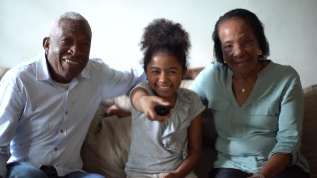 stockvideo's en b-roll-footage met grootouder en kleindochter tv kijken op de sofa thuis - latijns amerikaanse en hispanic etniciteiten