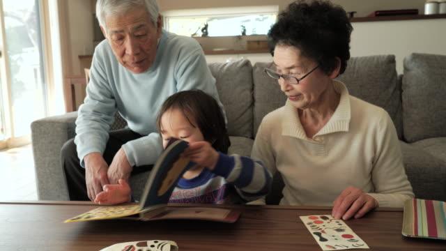 祖父母と孫が「リビングルーム」で楽しいひとときを - シニア点の映像素材/bロール