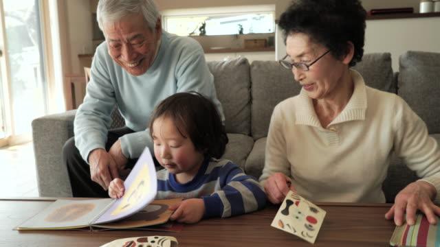 祖父母と孫が「リビングルーム」で楽しいひとときを - 家族点の映像素材/bロール