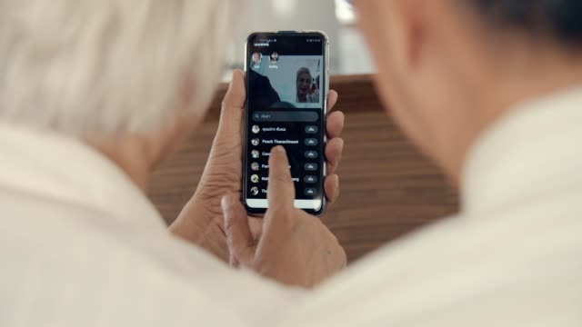 grandparent talks to grandchild on smart phone at home - video call with family video stock e b–roll