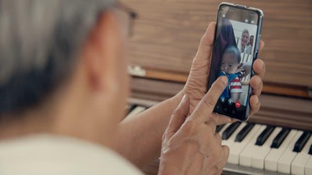 Grandparent talks to grandchild on smart phone at home