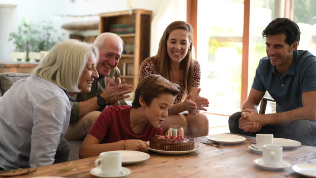 grandparents and father watching as boy blows out candles - bevanda calda video stock e b–roll