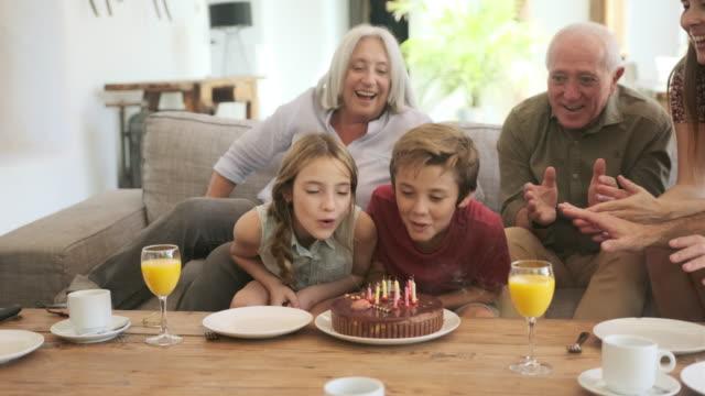 Grootouders en Vader kijken als jongen blaast kaarsen video