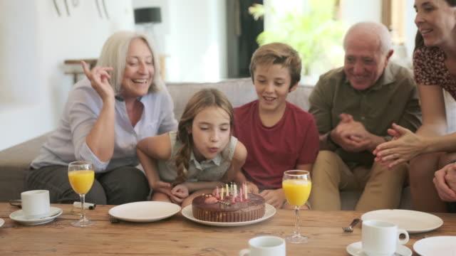 Grootouders en Vader kijken als meisje blaast kaarsen video