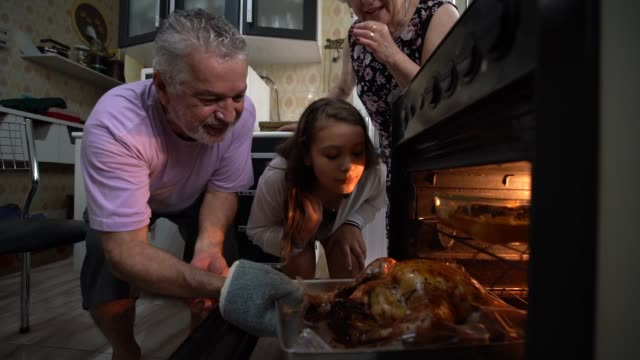 Grandparents and Granddaughter Checking the Traditional Turkey for Christmas Dinner