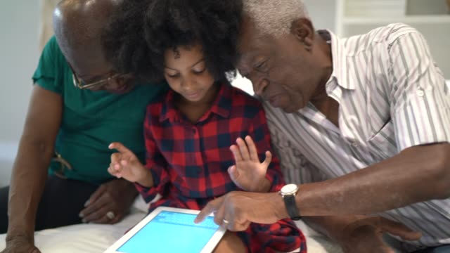 vídeos de stock, filmes e b-roll de avós e neta que usam a tabuleta digital na cama - mobile