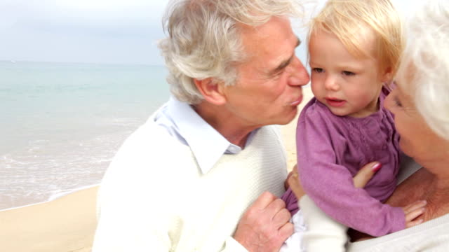 Grandparents And Granddaughter Walking Along Beach Together video