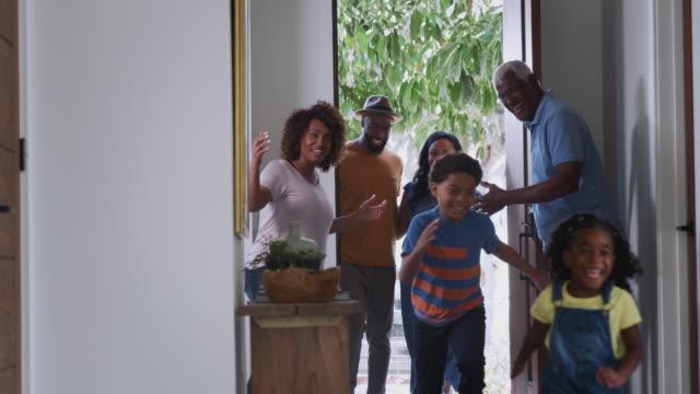 großeltern zu hause öffnen tür zu besuch familie mit kindern - grüßen stock-videos und b-roll-filmmaterial