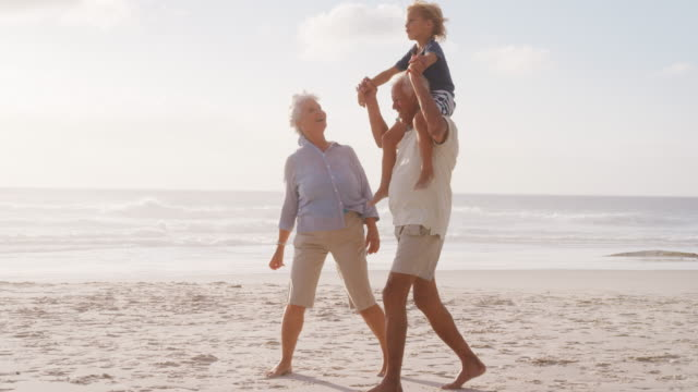 grandparents carrying grandson on shoulders as they walk on beach - grandparents stock videos & royalty-free footage