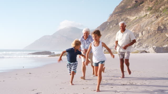 grandparents chasing grandchildren along beach on summer vacation - grandparents stock videos & royalty-free footage