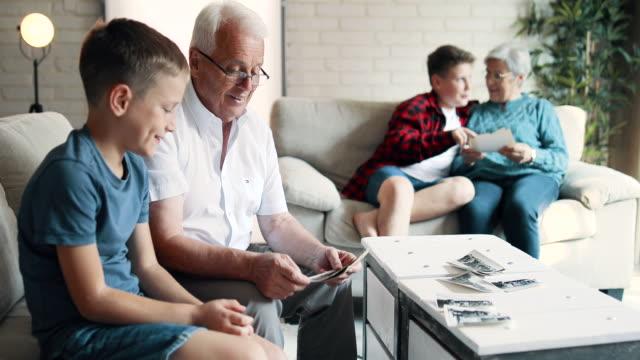 vídeos y material grabado en eventos de stock de abuelos charlando con nietos mirando álbum de fotos - árboles genealógicos