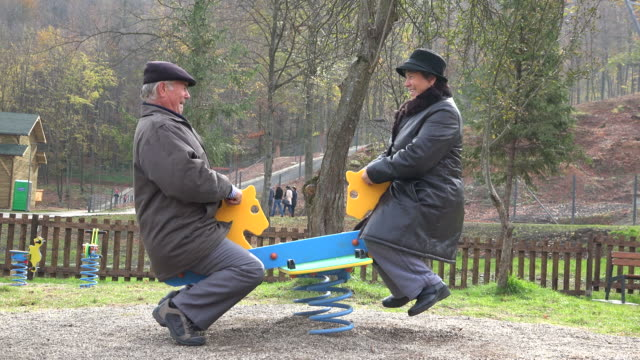 Grandparents couple having fun at child playground, smiling laughing in nature Grandparents couple having fun at child playground, smiling laughing in nature rocking chair stock videos & royalty-free footage