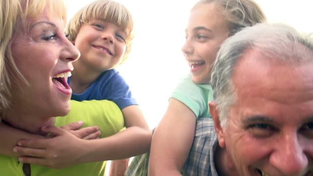 Grandparents Giving Grandchildren Piggyback Ride In Garden video