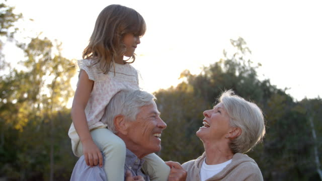 grandparents giving granddaughter a shoulder ride in park - grandparents stock videos & royalty-free footage