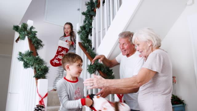 stockvideo's en b-roll-footage met grootouders groeten opgewonden kleinkinderen dragend pyjama's trap holding kousen op kerstochtend rennen - christmas tree