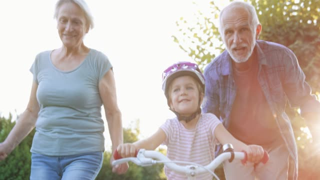 SLO MO Grandparents helping granddaughter ride the bike for the first time and cheering for her Slow motion wide dolly shot of a little girl riding her bike for the first time on a sunny street with the help of her grandfather and grandmother running beside her and cheering. Shot in Slovenia. granddaughter stock videos & royalty-free footage