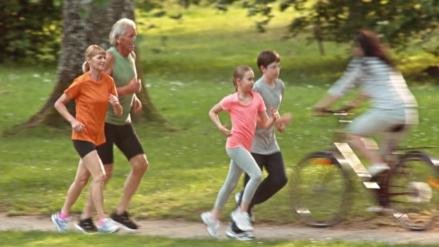 TS Grandparents jogging with grandchildren through a sunny park Wide tracking shot of A senior man and woman jogging through park with their grandson and granddaughter running in front of them. tank top stock videos & royalty-free footage