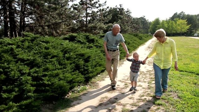 Avós levantando menino da criança ao ar livre - vídeo
