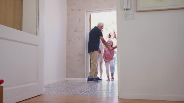 mor föräldrar öppna dörren till huset för att välkomna flera generationer familj på besök - ytterdörr bildbanksvideor och videomaterial från bakom kulisserna