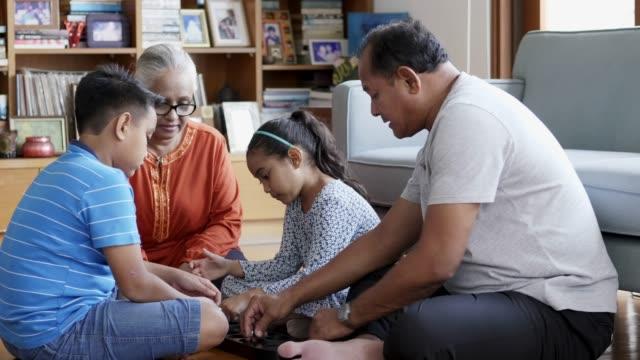 grandparents playing board game with grandchildren - развлекательные игры стоковые видео и кадры b-roll