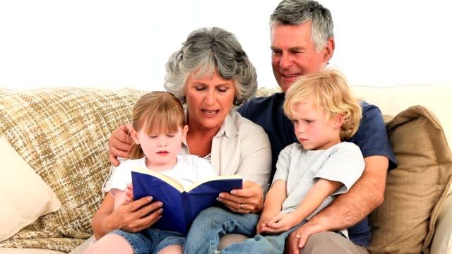 Grandparents reading a book to their grandchildren video