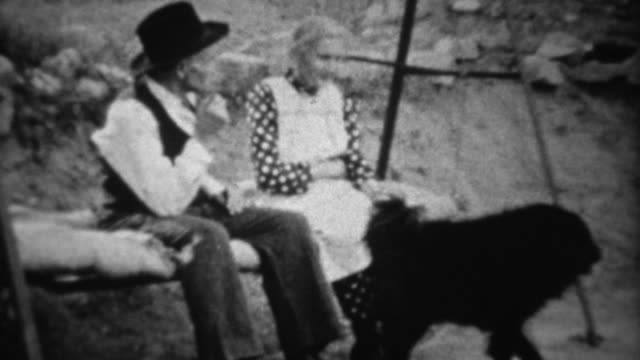 1939: Grandparents rocking on porch swing with black dog. video