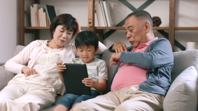 デジタル タブレットを使用して自分の孫と祖父母が座っていた - シニア点の映像素材/bロール