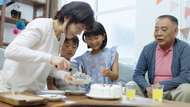祖父母が子供たちのパーティーでケーキを提供 ビデオ
