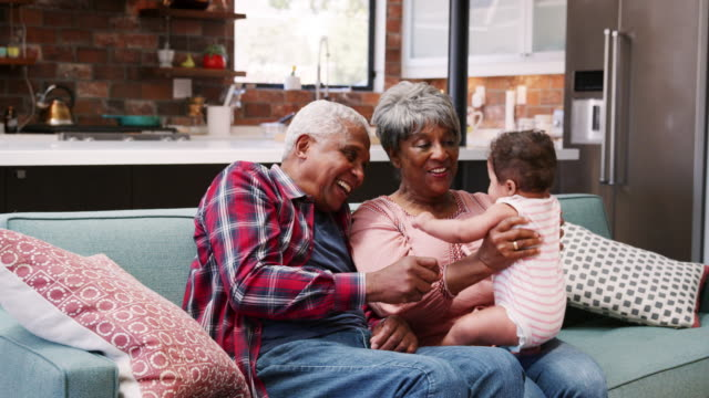 grandparents sitting on sofa at home looking after baby granddaughter - shot in slow motion - babka dziadek i babcia filmów i materiałów b-roll