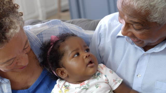 Grandparents Sitting On Sofa At Home With Baby Granddaughter video