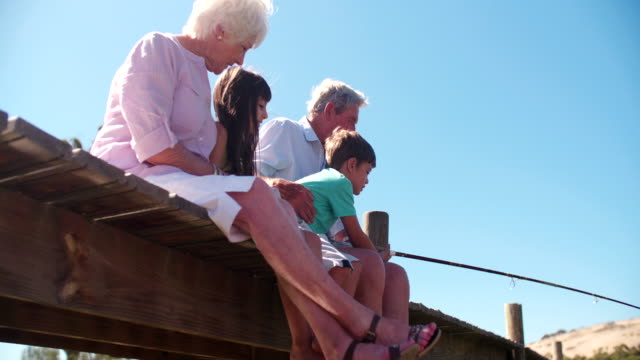Grandparents sitting with their grandchildren on a jetty video