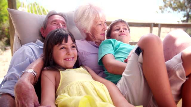 nonni trascorrere del tempo con i propri nipoti in amaca - amaca video stock e b–roll