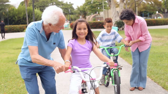 Grandparents Teaching Grandchildren To Ride Bikes In Park video