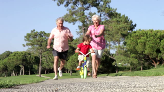 Grandparents Teaching Grandson To Ride Bike In Park video