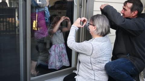 nonni in visita ai bambini in famiglia sul balcone durante il covid-19 - accudire video stock e b–roll