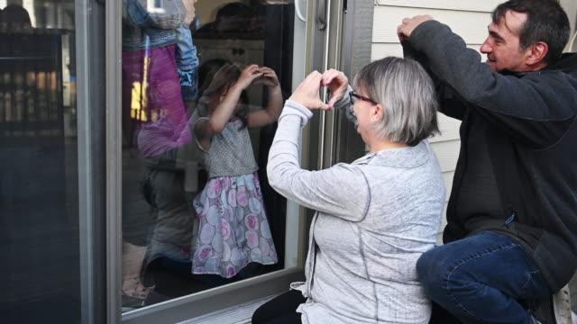居心地の良い-19の間にバルコニーで家族の子供を訪問する祖父母 - 抱きしめる点の映像素材/bロール