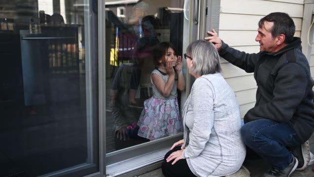 stockvideo's en b-roll-footage met grootouders die familiejonge geitjes op balkon tijdens covid-19 bezoeken - raam bezoek