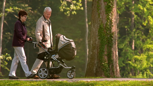 SLO MO Grandparents walking in the park with their grandchild in a stroller video
