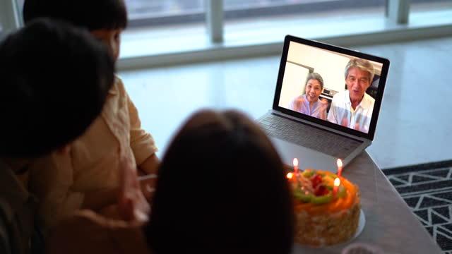 祖父母はビデオ通話を使用して孫の幸せな誕生日を願っています - 人里離れた点の映像素材/bロール
