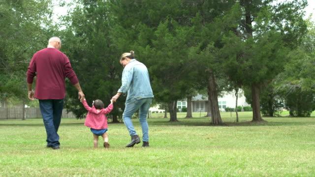 grandparents with baby learning to walk - nonna e nipote camminare video stock e b–roll