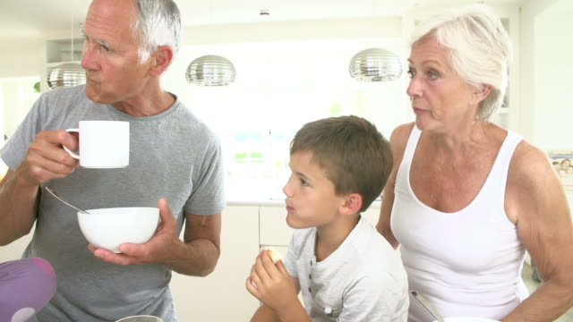 Grandparents With Grandchildren Eating Breakfast In Kitchen video